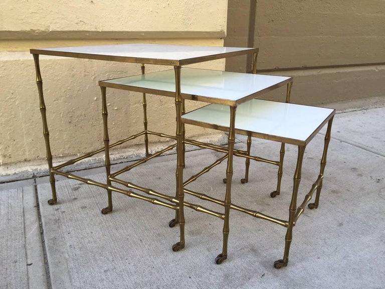 Bronze nesting tables by Maison Bague`s. Tables have bronze, faux bamboo frame on casters with milk glass tops. Larger table measures: 19