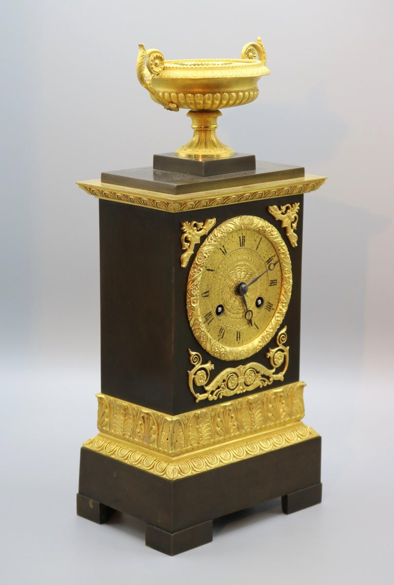 An early 19th century French bronze and ormolu eight day silk suspension striking clock contained in ornate case surmounted by well-cast and gadrooned urn with scroll carrying handles.