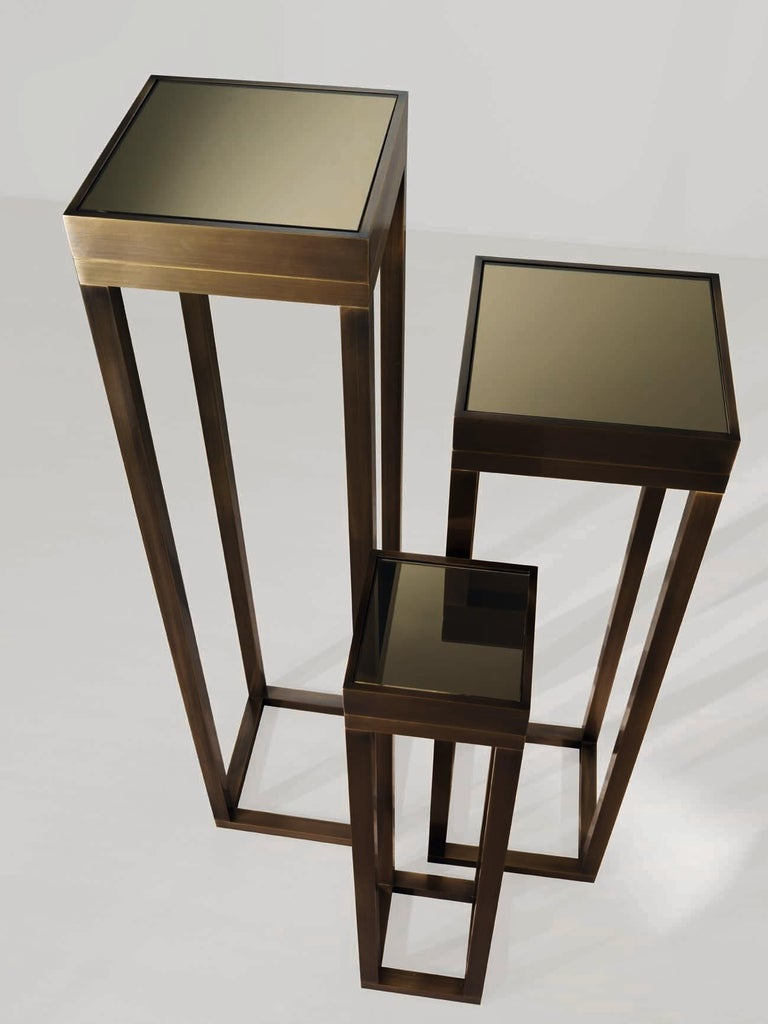 Bronze frame with bronzed mirror top and adjustable feet.
