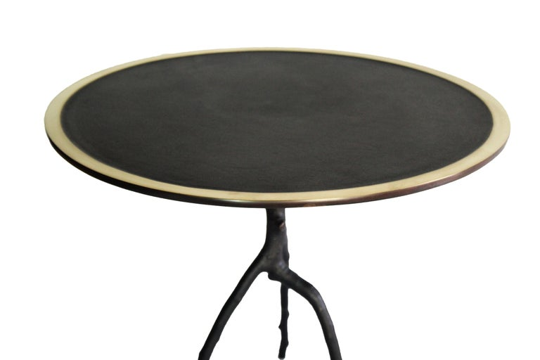 This handcrafted low table is made in France. With a apple tree branch as leg and a round tray with a polished contour, this side table is patined in black. Each table is signed and numbered. This side table belongs to the Bronze Sauvage collection
