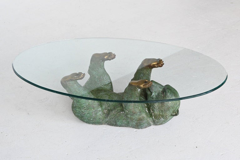 Beautiful and unique bronze bear coffee table in Hollywood Regency style, Belgium 1970. This sculptural coffee table is very detailed made of cast bronze and has a very nice patinated green color. The feet are made of brass and supporting an oval