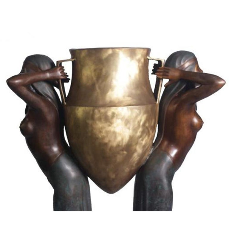 A contemporary cast bronze urn in polychrome patina depicting two bare-breasted Egyptian women. Featuring a beautiful polychromy contrasting golden tones with darker ones, this tall urn presents a striking image of two bare-breasted Egyptian women