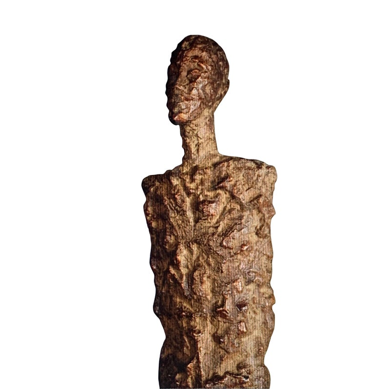 Indonesian textured bronze patina sculpture of a male figure. She is sculpted in an elongated shape in the style of Giacometti. The figure stands on a bronze base. Stands on bronze base measuring 3