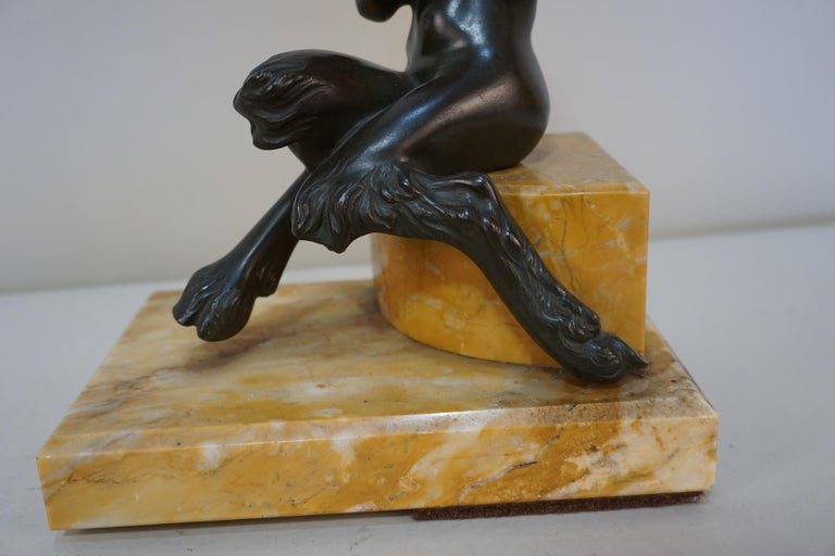 Bronze sculpture of young man playing a flute. Dark brown or green patina with marble base.