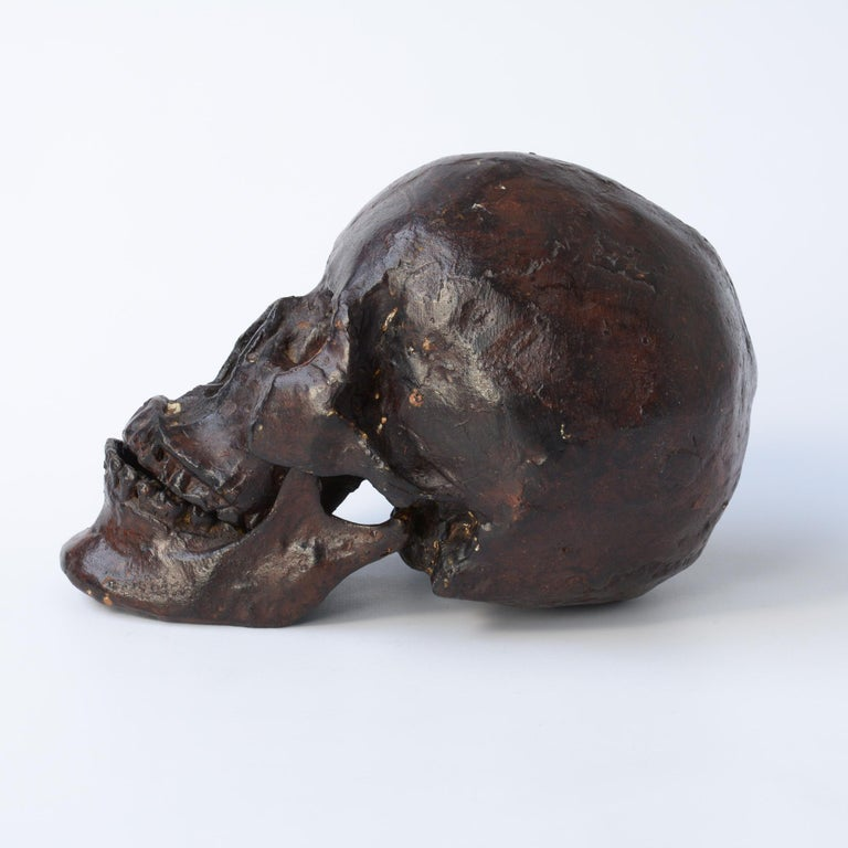 This bronze skull sculpture can be dated in the late 20th century. The bronze skull was made with the lost-wax casting methode. The model must have been a real human skull. The skull is made in 2 parts, the skull and the lower jaw. The lower jaw is