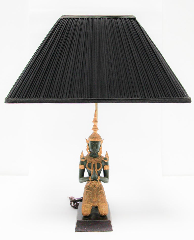 Bronze statue of a Thai Teppanom kneeling Angel Buddha made into a table lamp. Intricate bronze Thai Teppanom Kneeling Angel Buddha sculpture dark green with gold leaf detailing.  Thai gilt hand cast Buddha figure lamp, circa 1940. This bronze