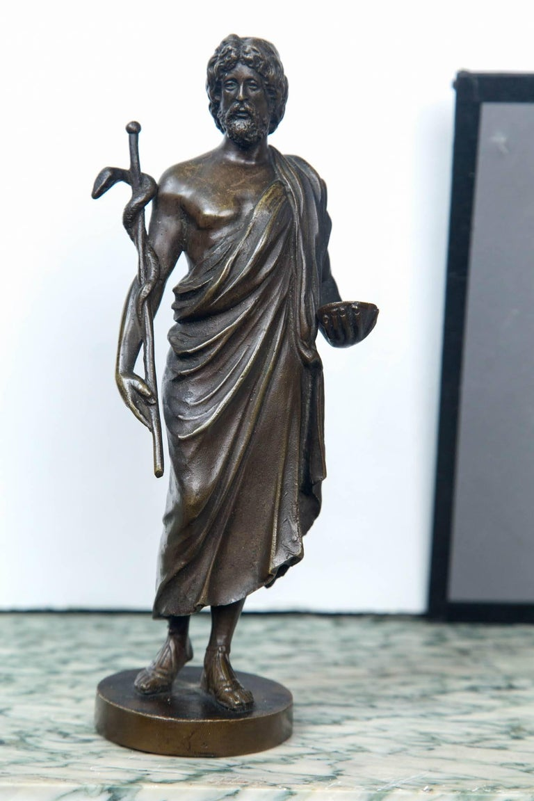Standing upon a base, the patinated statue holds a staff cradled in his right hand and arm, with a snake wrapped around it. (the cadeusus). In his left hand he holds a bowl. He wears a toga  On the back side of the base is the name Benetti. We
