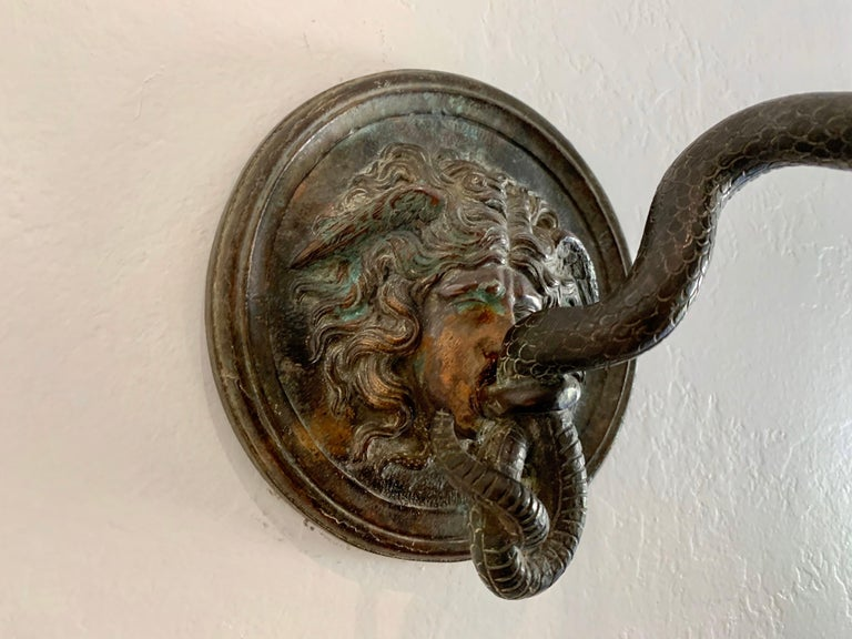 A most unusual cast bronze wall hook with the face of Medusa and a scrolled snake with hook. Nice dark patina in great antique condition. Stamp impressed upon foundry frame (see detail images). Theme is based on the story of Perseus and Andromeda,