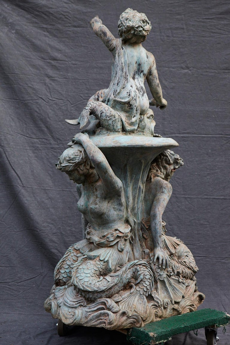 Bronze water garden/fountain statue of a merman and a mermaid carrying a merboy and a dolphin on their shoulders. The statue has a wonderful, lovely green patina. The statue is piped.  Additional photos can be provided on request, as the space is