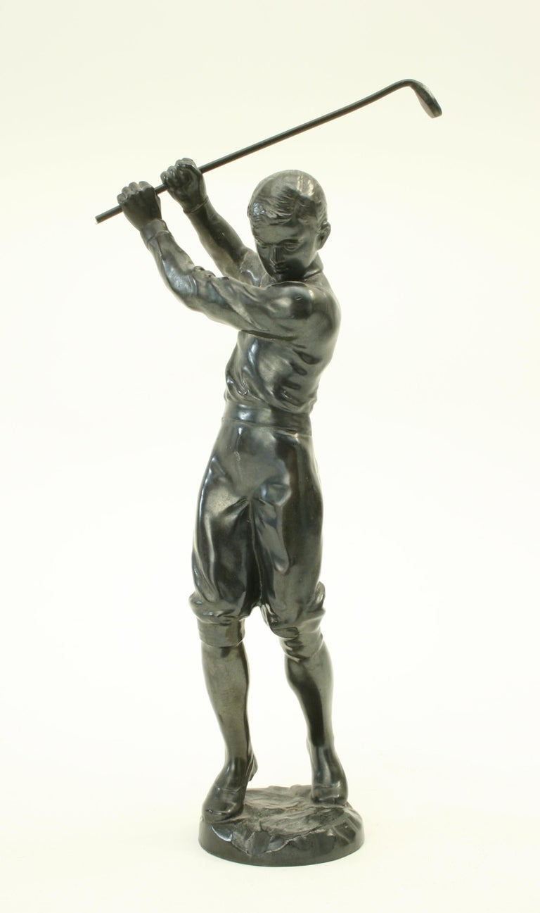 Bronzed statue of a boy golfer. A very nice, well modelled figure of a boy playing golf. He is in a full back swing position with an old fashioned two handed grip (baseball grip). The figure is made of spelter with a dark bronze finish.