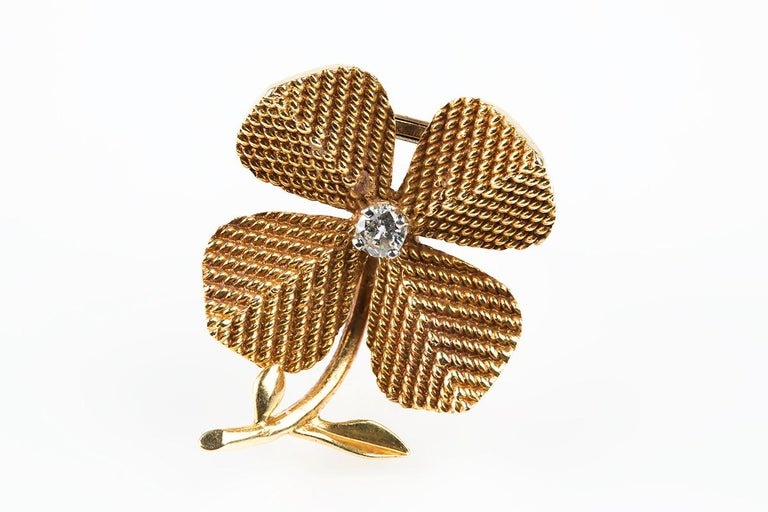 An 18 karat yellow gold brooch in the form of a four leaf clover set with a centre,brilliant cut diamond, a double pin fitting behind with the makers mark of Sterle of Paris together with eagles head marks.Measuring 23 mm in width