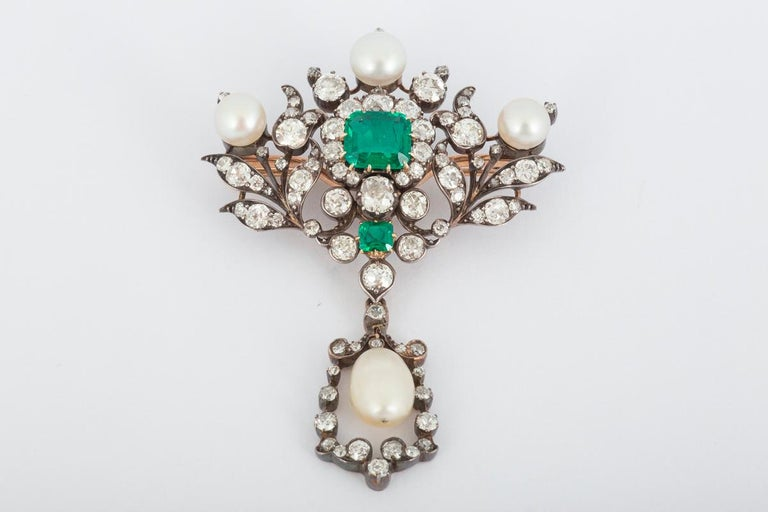 An important ,19th century,Columbian Emerald,old cut brilliant Diamond,and natural pearl floral brooch with detachable fitting, to be worn as a pendant also.Mounted in silver and 18carat yellow gold.The fine coloured Emerald centre weighing
