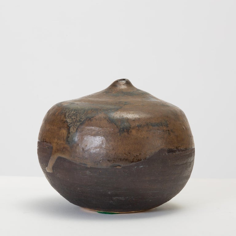 """A simple, studio pottery weed pot or bud vase with a thick chocolate brown gloss glaze over a matte ebony glaze. Ceramic underneath is revealed on foot and engraved with the artist's name """"Sakamoto.""""  Condition: Excellent vintage"""