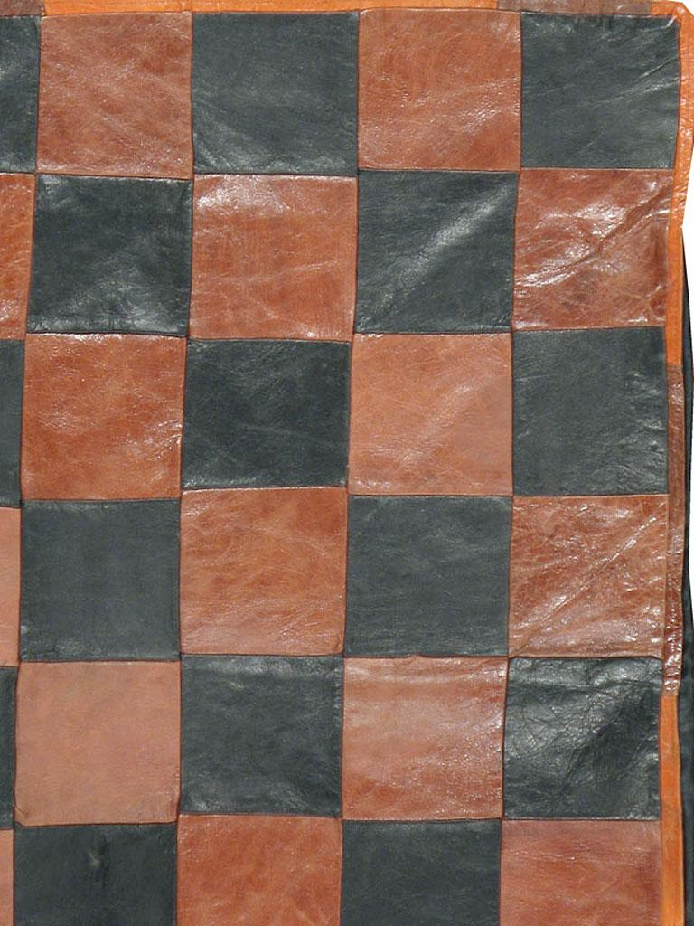 A vintage Italian Art Deco rug from the mid-20th century. A true oddity. Brown and black leather squares alternate in a chessboard (checkerboard) pattern on this totally modern scatter rug handmade in Italy. A very unusual, yet versatile piece for a