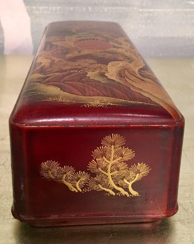 A brown and red lacquer box with design of hawk, pine tree and river.