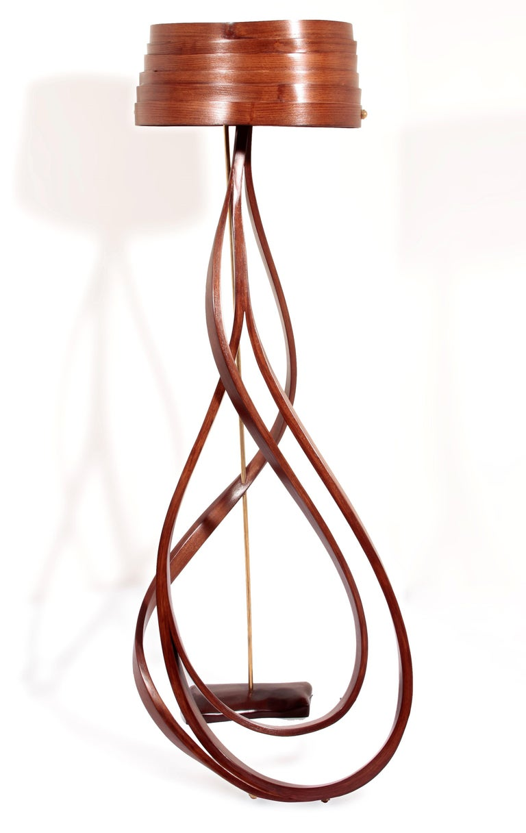 This floor lamp has been made by bending solid wood in layers of loop-like designs, merging at the top. The piece is supported by a polished brass rod creating a two-tone color palette. The lamp shade is fully constructed using thin strips of solid