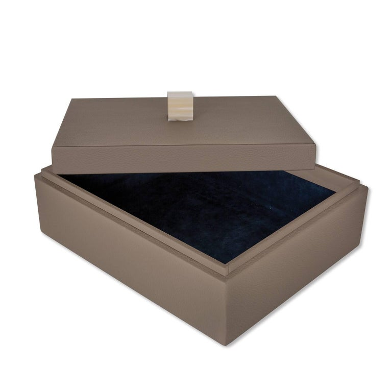 Versatile and sophisticated, this elegant box is a precious addition to any modern or contemporary home. Crafted of wood, its rectangular silhouette and lid are covered by hand with brown fine grain leather. Available in five different colors, this