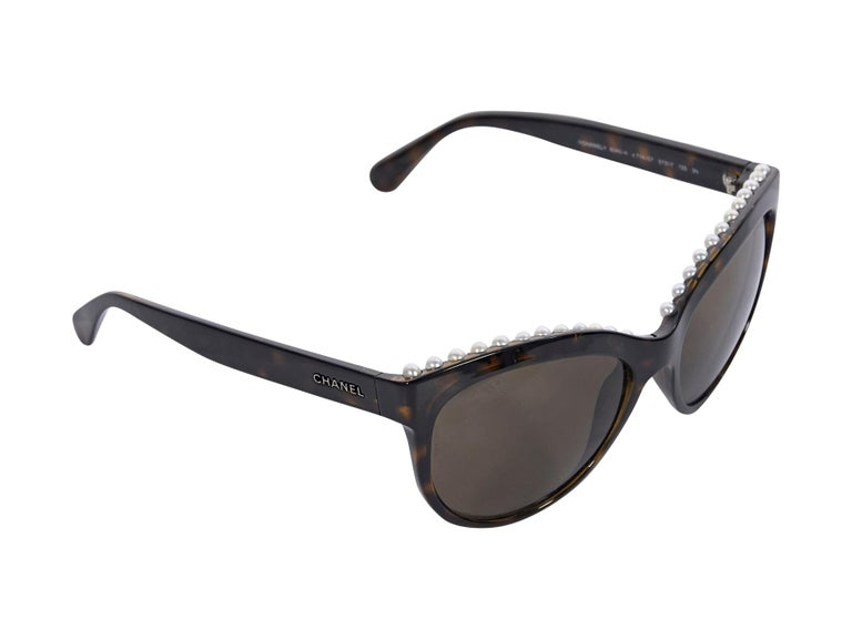 Product details:  Brown tortoiseshell cat-eye sunglasses by Chanel.  Trimmed with faux pearls.  Logo detail at temples.  2.5