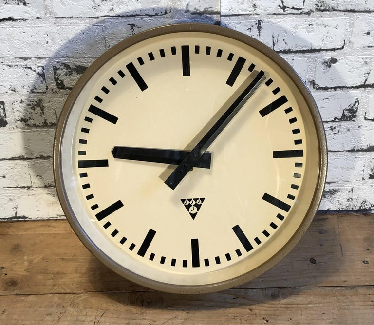 Pragotron wall clock made in former Czechoslovakia during the 1960s. It Features a brown hammer paint metal frame, iron dial and clear glass cover. The piece has been converted into a battery-powered clockwork and requires only one