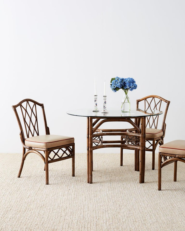 Organic modern style Brown Jordan round dining table or breakfast table. Constructed from bamboo and rattan frame decorated with stretchers having a lattice design on each side. Topped with a pane of round glass and supported by double rattan legs.