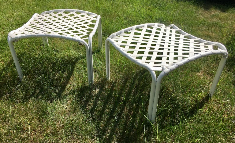 Pair of Mid-Century Modern outdoor patio or deck ottoman stools by Brown Jordan. White tubular curved aluminum frames feature original white vinyl strapping in a cross-lace pattern. Original Brown Jordan labels and item numbers on frames. Perfect