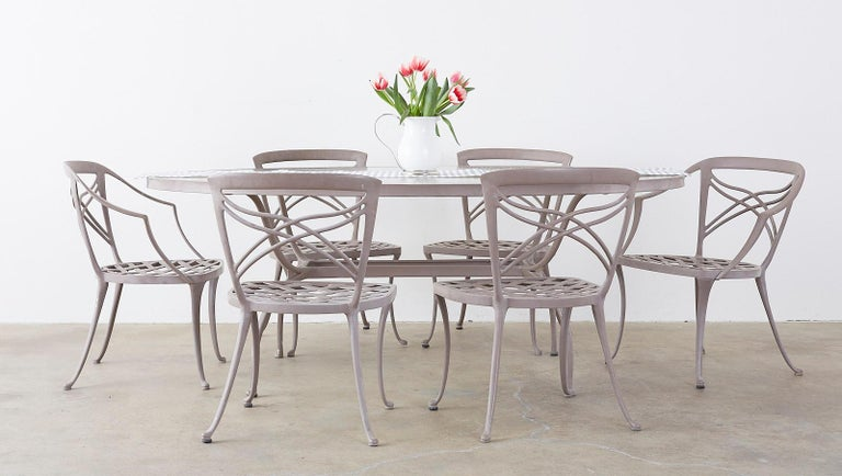 Elegant powder coated aluminum patio or garden table made by Brown Jordan in the neoclassical style. Features a large oval frame inset with a piece of textured glass. Supported by klismos style legs with graceful curves that conjoin in the center