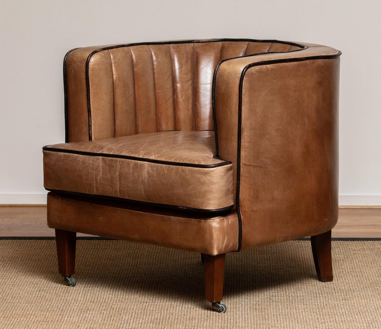 Beautiful Scandinavian leather lounge / easy / club chair in brown leather with black piping's, Denmark, 1950s. This chair is extremely comfortable and supports very well. The leather is in good condition and the old patina gives this chair warm