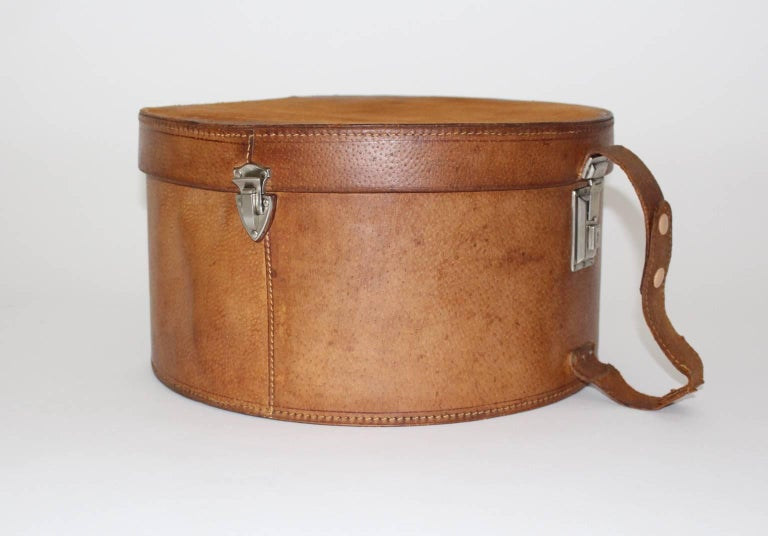 Wonderful leather case from the 1950s. One snap-lock and two locks and a carrying strap. Great leather patina Labelled Max Feichtinger Graz Jakominiplatz Very good condition with minor signs of age and use. approx. measures: diameter 42 cm height 23