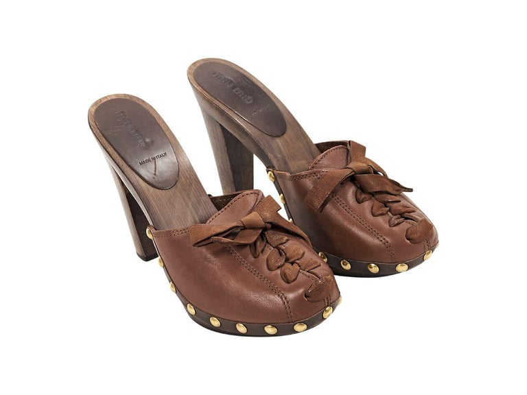 Product details:  Brown leather heeled mules by Miu Miu.  Accented with studs.  Lace-up front panel.  Round toe.  Wooden heel and platform.  Slip-on style.  Goldtone hardware.  5