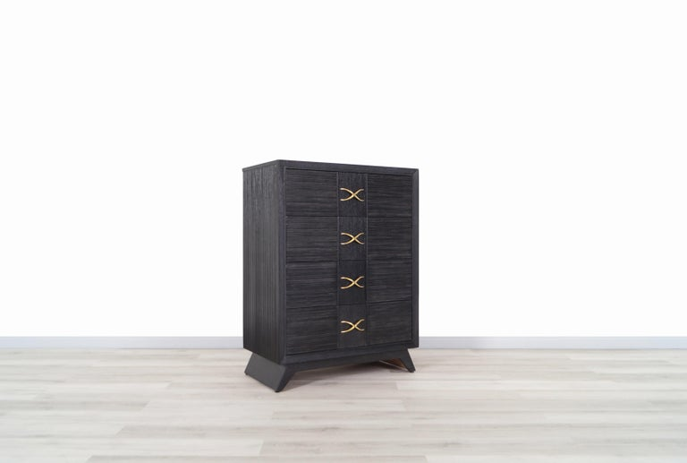 Vintage chest of drawers / tall dresser designed by Paul Frankl for Brown Saltman, circa 1950s. This beautiful chest of drawers features four large pull-out dovetailed drawers, all integrated with original brass X pulls. Its spacious drawers make it