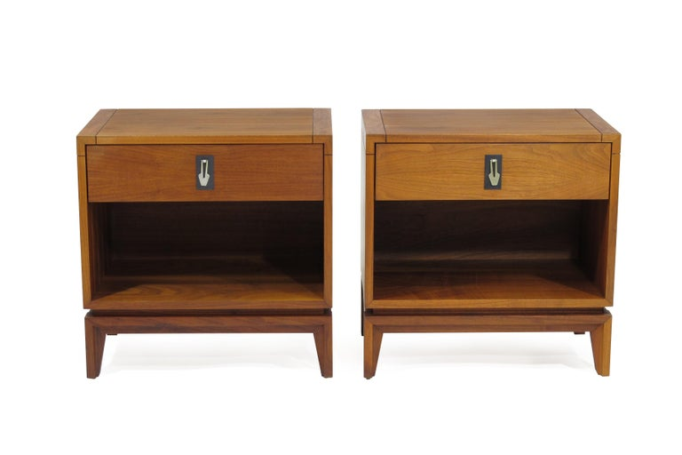 Midcentury walnut nightstands by Brown Saltman. One-drawer with metal drop-pull over an open space for storage, raised on tapered legs.
