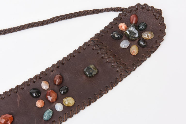 This gorgeous never used brown stitched leather tie belt has assorted cluster of beautiful agate stones in different colors. There are dimensional and raised.  The colors are varied and are in hues of orange, light yellow, shades of green, black,
