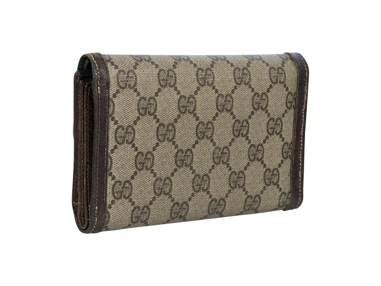 Product details:  Vintage brown canvas printed trifold wallet by Gucci.  Leather-trimmed. GG diamanté logo-patterned. Snap closure.  Lined interior with multiple credit card slots and ID slot. 6.75
