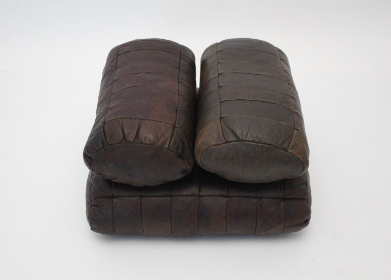 This set of four pillows by De Sede Switzerland, 1970s were made of chocolate brown leather stitched patchwork and features a great leather patina.