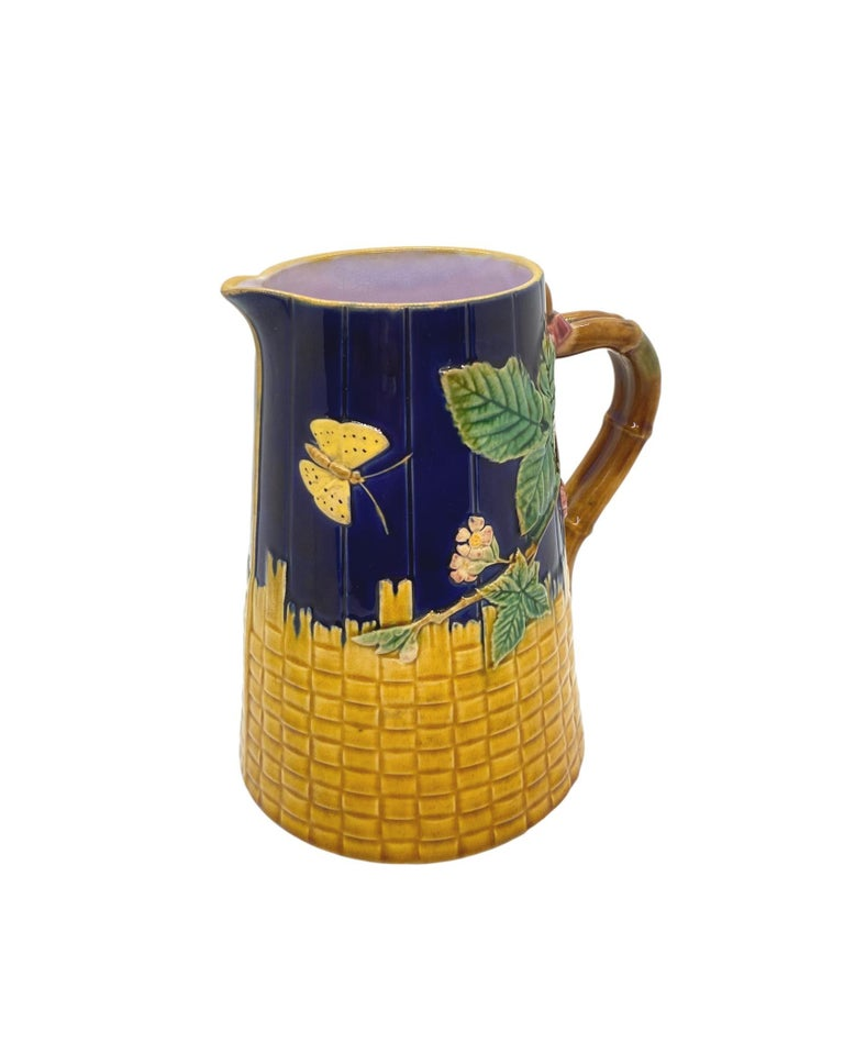T. C. Brown-Westhead Moore & Co. Majolica Butterfly Pitcher, on cobalt blue-glazed simulated wooden staves and Yellow Basketweave, with faux bamboo handles, the interior glazed in lavender, the reverse with British Registry Mark for 19 September