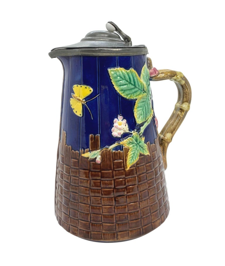 T. C. Brown-Westhead Moore & Co. Majolica Butterfly Pitcher, on cobalt blue-glazed simulated wooden staves and brown basketweave, with faux bamboo handles, the interior glazed in lavender, the reverse with British Registry Mark for 19 September