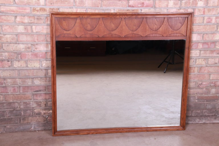 An exceptional Mid-Century Modern sculpted walnut framed mirror