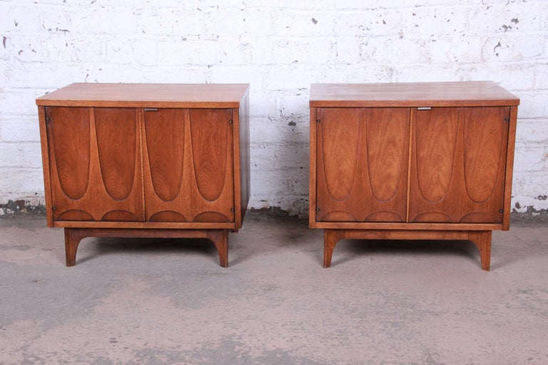 A stunning pair of Mid-Century Modern sculpted walnut nightstands or side tables by Broyhill Brasilia. The nightstands feature beautiful walnut wood grain and an iconic sculpted arch design. They offer good storage, each with an open cabinet space