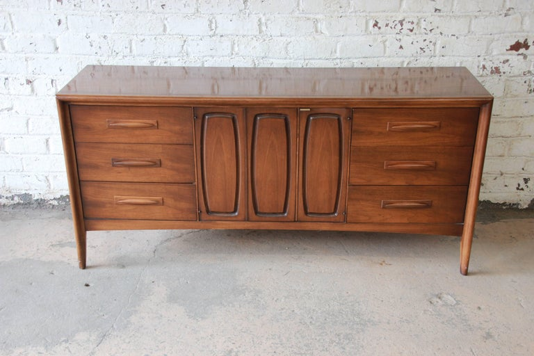 Offering a very nice Broyhill Emphasis Mid-Century Modern sculpted walnut credenza or triple dresser. The credenza has clean midcentury lines, beautiful walnut wood grain, and nice sculpted walnut drawer pulls. It offers ample room for storage, with