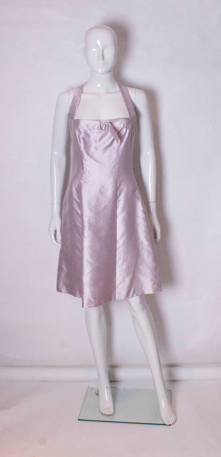 A chic cocktail dress by British designer Bruce Oldfield. The dress is in a pale lilac/ silver silk, and is fully lined. The dress has an interesting t detail at the back and a diamante buck on the bust.
