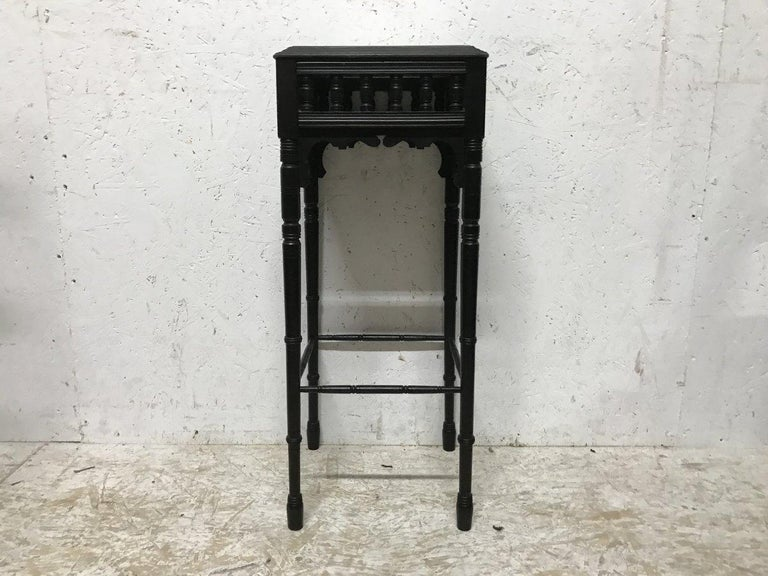 Bruce Talbert. An Aesthetic movement ebonized plant stand, with turned details and gilt highlights, inset with a hand-painted Minton pottery tile decorated with Cherry Blossom and if you look closely three little black and white ladybirds, with a