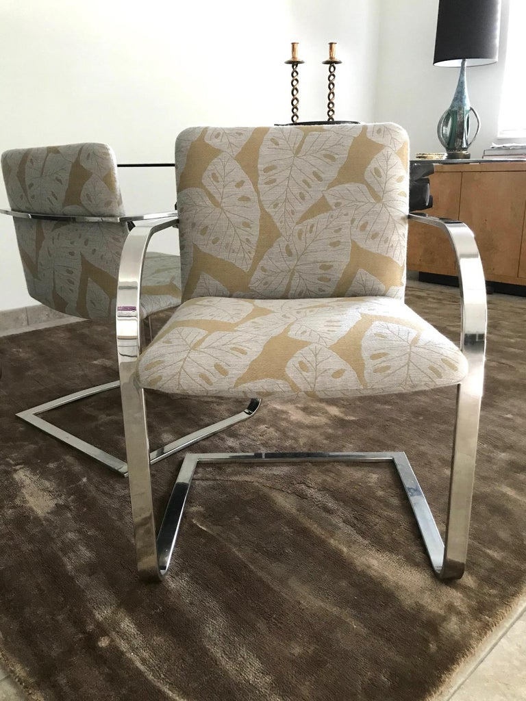 Mid-Century Modern desk chair or side chair with cantilevered steel frame in chrome. Chair has streamlined profile with curved armrests and floating seat design. Newly upholstered in handwoven fabric with bold tropical leaf print in hues of taupe