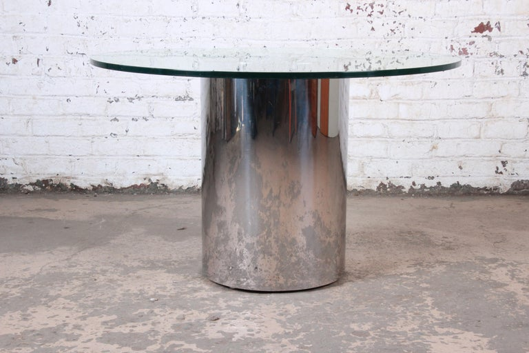 A sleek and stylish Mid-Century Modern drum base pedestal dining or center table  By Brueton  USA, circa 1970s  Polished steel base and thick glass tabletop  Measures: 48