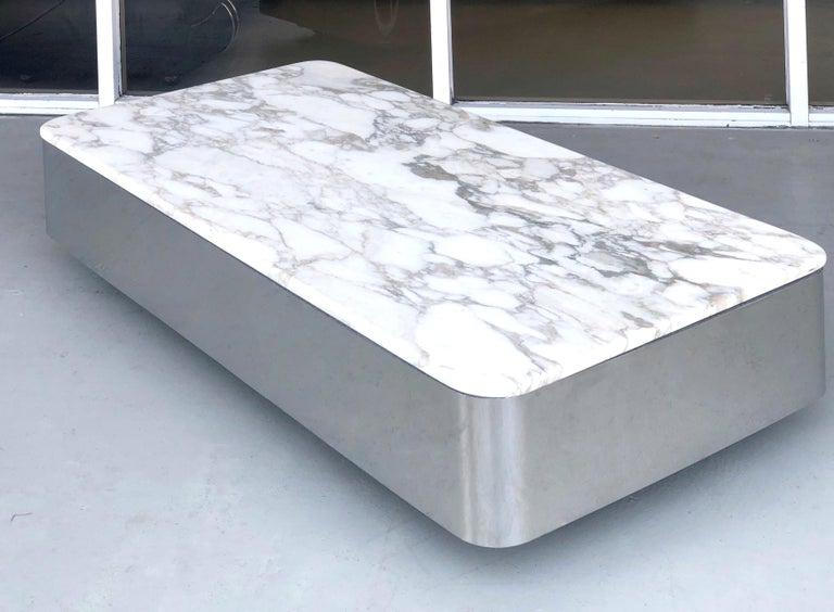 A low floating coffee table by Brueton. Polished stainless steel with a thick honed marble top. It is on casters for easy mobility, table seems to levitate.