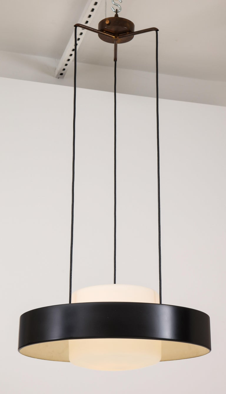Stilnovo iconic chandelier model 1158 composed of black enameled metal ring and opaque glass shades suspended from original brass canopy and structure, Italy, 1960s. This adjustable ceiling light emits light beautifully with its opaque glass shades