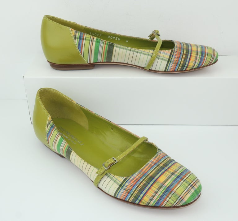 Bruno Magli's preppy version of classic Mary Jane shoes combines an avocado green leather heel and strap with a girlish plaid fabric in shades of spring green, yellow, blue, black, orange and off-white.  The strap offers a three hole adjustment with