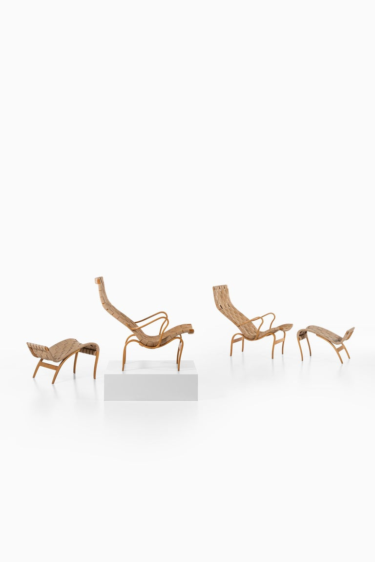 A pair of easy chairs with stools model Pernilla designed by Bruno Mathsson. Produced by Karl Mathsson AB in Värnamo, Sweden.