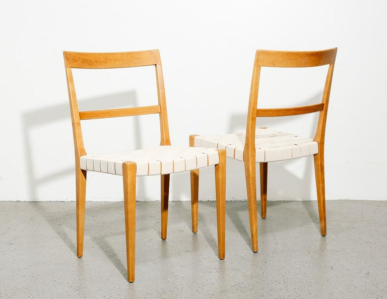 'Mimat' dining chairs designed by Bruno Mathsson for Mathsson International, Sweden. Wonderfully minimalist form with subtle tapering. Beech frame with new off-white canvas webbing. Sold individually.  Measure: 17.75