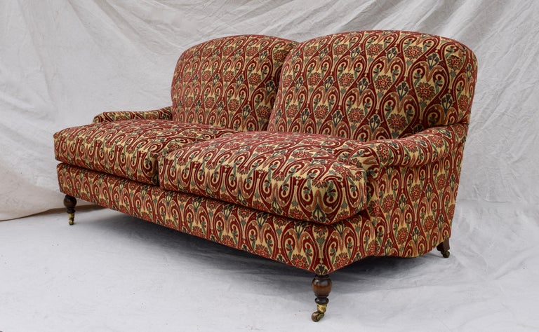 Luxurious two-seat sofa upholstered in lushly textured needlepoint tapestry style B & F fabric. Rolled arms, generously filled goose down cushions with turned mahogany front legs on brass castors are among many exceptional features offering an