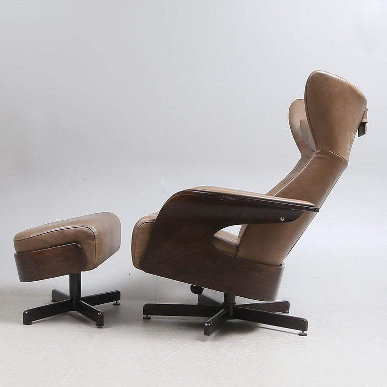Leather and hardwood Amanda armchair with ottoman, foot crosses made of matte chrome-plated steel, swivel base. Loose neck pillow and seat cushion. Adjustable seat and back. Measures: H 100, W 82 cm. Made by Brunstad Møbler in Norway in the 1990s.